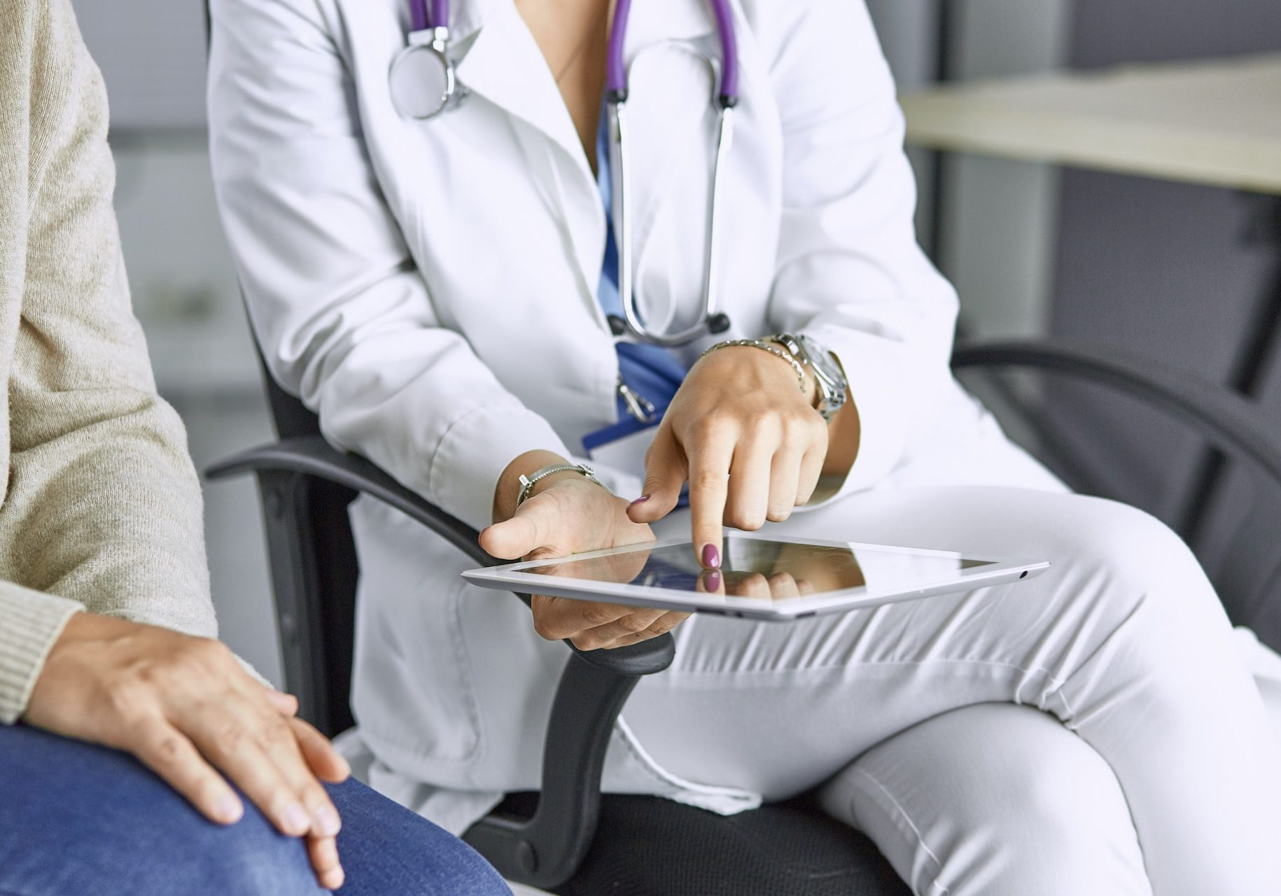 female doctor talking to a patient on a tablet.